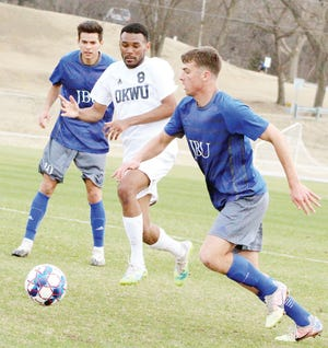 Mattheus Ferreria, center, of Oklahoma Wesleyan University mixes it up in a battle for the ball during 2020 season action. (Mike Tupa/Examiner-Enterprise)