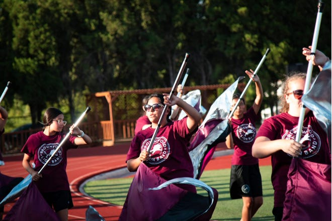 Members of the Brownwood High School marching band's color guard are pictured during the Meet the Lions event Friday evening at Gordon Wood Stadium. Behind the pageantry and precision of the color guard are hard work and lots of  practice. Meet the Lions featured the band and color guard, cheerleaders, Lionettes and the introductions of players and coaches.