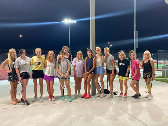 The Andover Central girls' tennis team poses for photos after their annual midnight practice to kick off the new school year. It is the seventh annual event and the first at their new tennis facility.