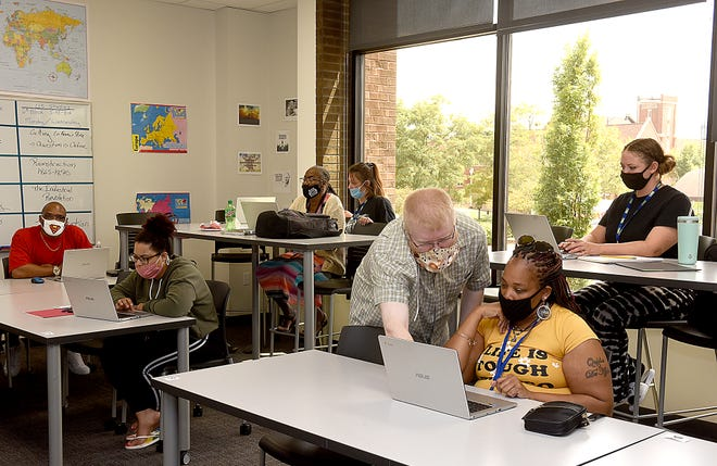 Goodwill Excel Center of Columbia astronomy teacher Peter Reed helps student Shalonda Cain in class on Monday.