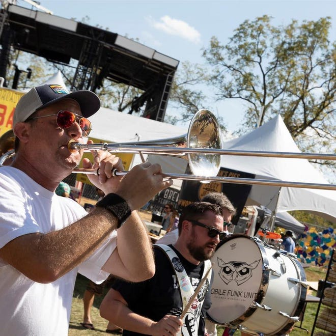 Mobile Funk Unit members Travis Huff (trombone) and Ryan Hobart (percussion) play at the 2019 Roots N Blues festival.