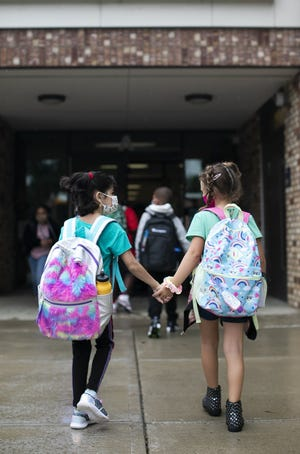Students head into school on the first day back to school at Pickerington Elementary School, Monday, August 16, 2021.