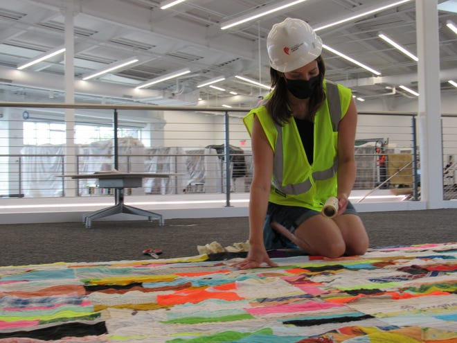 Artist Andrea Myers inspects a quilt she was commissioned to make for the Karl Road branch of the Columbus Metropolitan Library. The quilt, which will be displayed on the second floor, was stitched together using fabric donated by people in the neighborhood. Some of the panels display the names of community spaces, such as Woodword Park. A grand-opening ceremony is scheduled Sept. 9 at 5590 Karl Road in north Columbus.