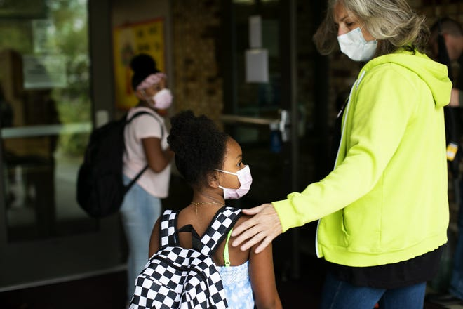 Aminata Reynolds, 8, is ushered into school by gifted teacher, Vicki Westwood, on the first day of school at Pickerington Elementary School on Aug. 16. Pickerington schools is requiring masks for all K-6 students, and is strongly encouragingbut not requiring them for students in grades7-12.