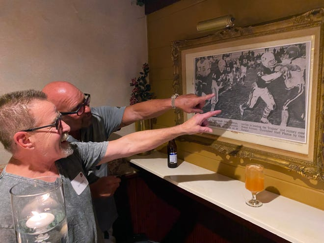 Former St. Mary's High School fullback Bill Roach, foreground, and running back Johnnie Luteran reminisce as they look at a photo from The Examiner that depicts Roach throwing a block for Luteran in the playoffs that season. Luteran scored the lone touchdown in a 6-0 Class 2A state championship over St. Louis Country Day in 1972.