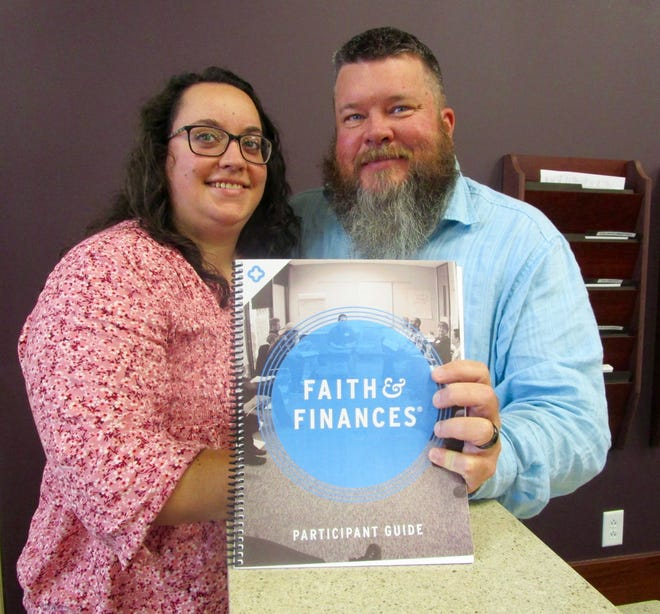 Doug and Heather Kuriger show the book they will use in leading a class, Faith & Finances, beginning Thursday, Sept. 2, at First United Methodist Church in Geneseo.