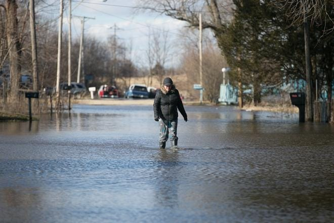 Freeport plans to use a nearly $3.4 million Federal Emergency Management Agency grant to purchase and demolish nearly 130 flood-prone homes east of the Pecatonica River. In this March 15, 2019, file photo, Allyson Hartman walks down a flooded Louis Avenue in Freeport after the river overflowed and flooded streets.