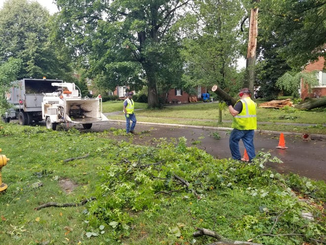 William O'Neal (left) and Scott Childers, employees for the City of Monroe Department of Public Services, use a wood-chipping machine to clear limbs and brush that fell along Hollywood Dr. last week.
