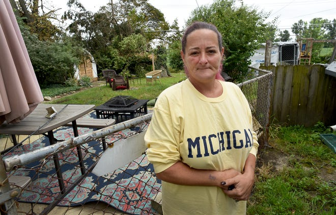 """Shara Ward of Monroe stands near the fence between her home and the home of her neighbor, Lorraine Virtue, where possible live wires are still located in their backyards off Michigan Ave. since the storm last Wednesday.""""The fireman will not even go back there,"""" said Ward. The yard to the left is Virtue's as a wire runs across the the middle of the yard."""