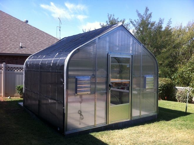 Galvanized steel-frame hobby greenhouse glazed with twin wall polycarbonate panels and covered with shade cloth ready for plants.