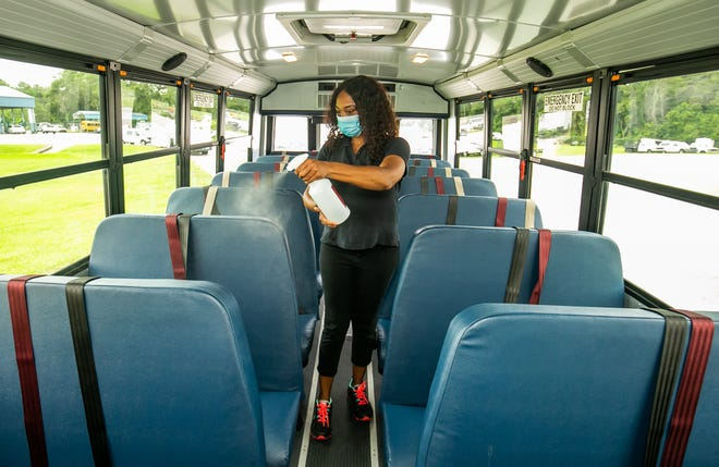 """Marion County Public School Bus Driver Terri Haynes, sanitizes her bus Monday afternoon before leaving the bus compound. """"We've done lost two drivers (to COVID),"""" Haynes said. The school district is currently facing a bus driver shortage amid high COVID-19 cases and quarantines in the first week of school."""
