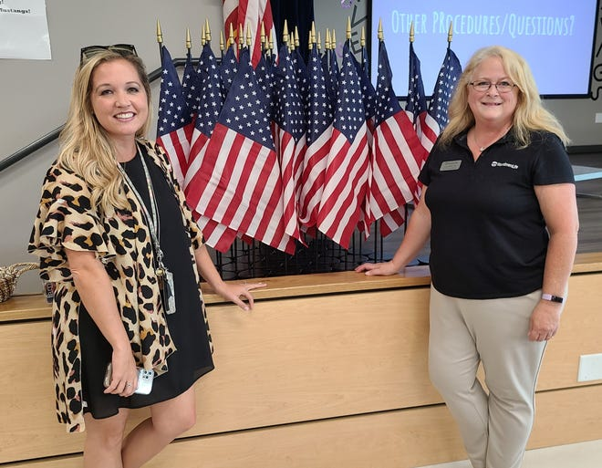 Summer Cox (left), principle of Oliver Springs Elementary School in Van Buren, was presented with 32 American classroom flags by Lynn Buck (right), Woodmen Life financial representative. The flags were donated on behalf of WoodmenLife Chapter 12 in Fayetteville.