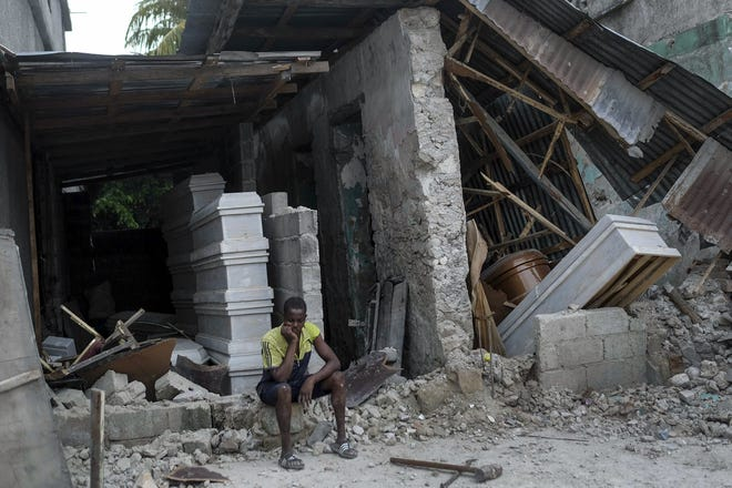 A man sits in front of a collapsed funeral home in Les Cayes, Haiti, Monday, Aug. 16, 2021, two days after a 7.2-magnitude earthquake struck the southwestern part of the country. (AP Photo/Matias Delacroix)