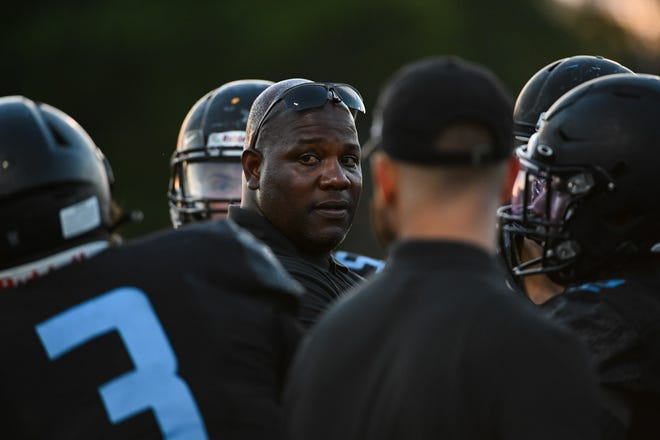 St. John Paul II coach Kelcey Brooks talks to his team during the spring football game against Pahokee in Boca Raton in May.