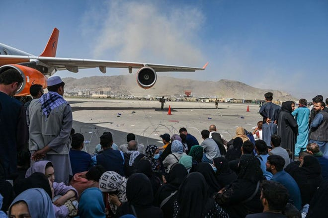 Afghan people sit as they wait to leave the Kabul airport in Kabul on August 16, 2021, after a stunningly swift end to Afghanistan's 20-year war, as thousands of people mobbed the city's airport trying to flee the group's feared hardline brand of Islamist rule. (Wakil Kohsar/AFP via Getty Images/TNS)