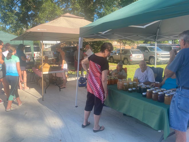 A patron makes a selection at Grosse Tete resident Neal Boudreaux's barbecue sauce booth. Boudreaux was among 24 vendors at the second Grosse Tete Farmer's Market on Saturday, Aug. 14 at Grosse Tete Memorial Park.