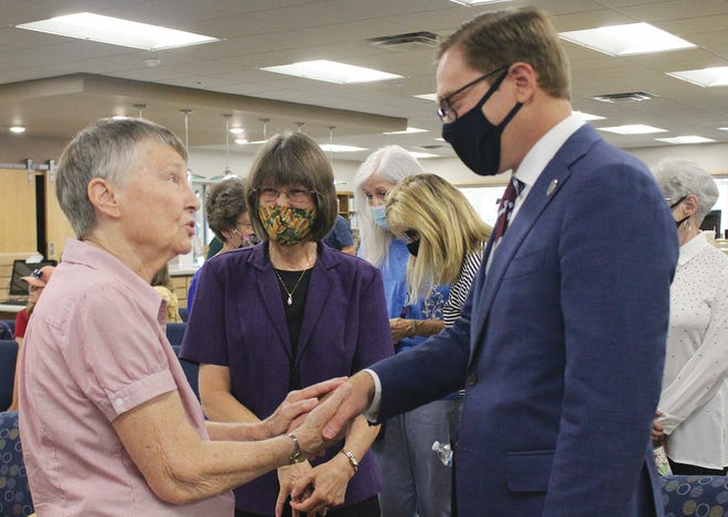 David Toland (right), meets and greets the public at a special library reception for 50-year employee Lea Ann Holland (middle) last Thursday in Pratt. Jean Mease shared words of wisdom with Toland, along with a handshake.