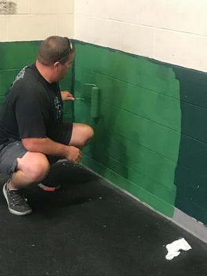 Pratt High School football coach Tyler Strong puts a coat of traditional Greenback green paint on the walls of the school's weight room. Donations made it possible for a renovation project for the weight room this year.