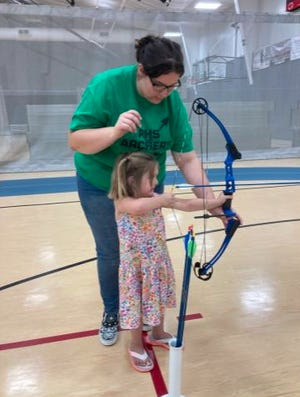 Pratt High School student Shauna Phye assists a young archer as she learns to properly hold and shoot a bow and arrow at the Blythe Family Fitness archery exposition last week in Pratt.