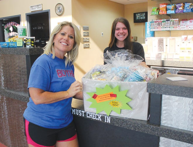 Kristina Kaufman and Ashlyn Hatley show a special box full of health and exercise-related items that was raffled off as part of the recent 10-year anniversary of Blythe Family Fitness in Pratt. The box was won by Mark Fuhr.