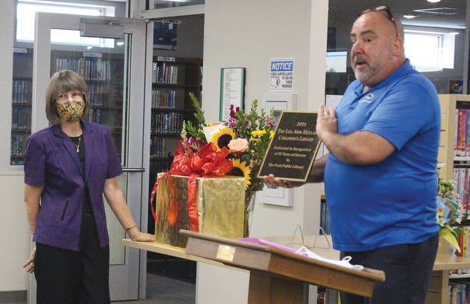Pratt Public Library director Eric Killough shows a plaque designating a new name for the library, The Lea Ann Holland Children's Library, in honor of Holland's (left) 50 years of service.