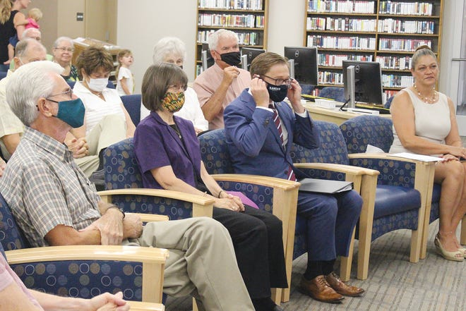 Donning a mask like most other participants, Kansas Lt. Gov. David Toland (third from left) takes part in a special library dedication in honor of Lea Ann Holland (second from left) last week in Pratt.