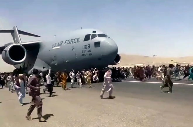 Hundreds of people run alongside a U.S. Air Force C-17 transport plane as it moves down a runway of the international airport, in Kabul, Afghanistan on Monday. Thousands of Afghans have rushed onto the tarmac at the airport, some so desperate to escape the Taliban capture of their country that they held onto the American military jet as it took off and plunged to death.