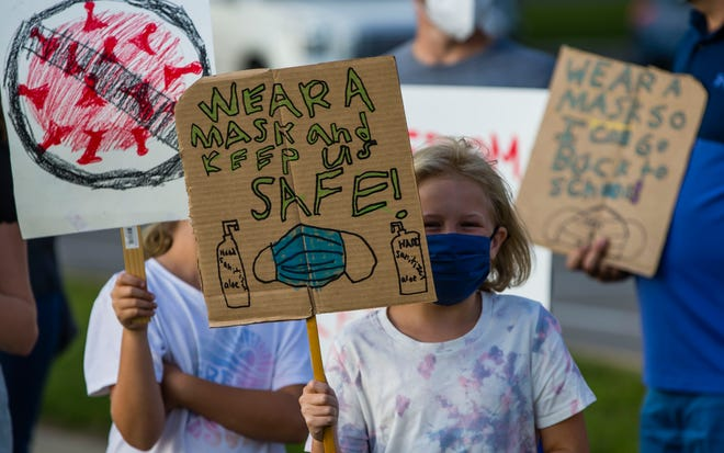 People hold signs in favor of wearing masks Monday near Penn High School on Bittersweet Road in Mishawaka.