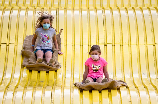 Lili Wallman, 7, center, heads down the Giant Slide with her sister Essa Wallman, 9, left, during the 2021 Illinois State Fair at the Illinois State Fairgrounds in Springfield, Ill., Monday, August 16, 2021. [Justin L. Fowler/The State Journal-Register]