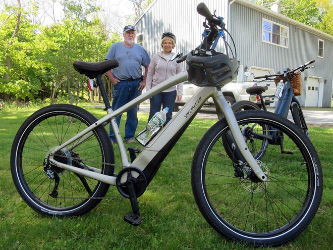 A couple shows their electric-assisted bicycles outside their home.
