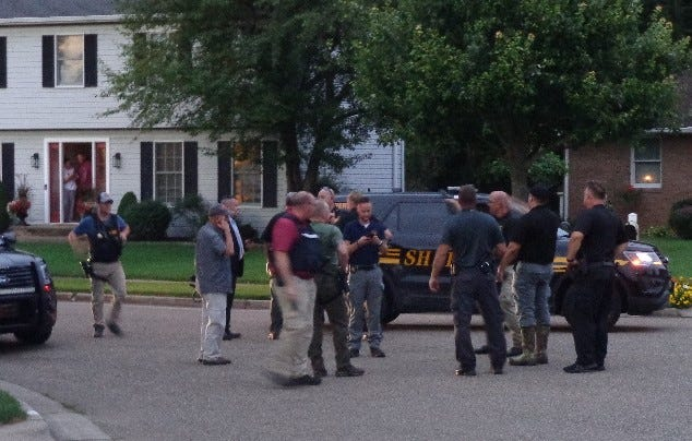 Law enforcement officers talk after capturing a second male juvenile Sunday night who escaped from the Multi-County Juvenile Attention Center in Canton earlier in the day.