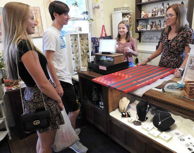 Nikki Springer and Anthony Williamson of Canton buy a wooden OSU flag sign at Canal Cargo in Roscoe Village from new owner Lindsey Olinger and her daughter, Grace. Lindsey and her husband, Chad, took over the store on Aug. 1 from Jeff and Lynette Wright, who owned it for 16 years.