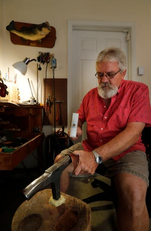 Doug Shemenski, president of the area chapter of the Florida Society of Goldsmiths, shapes one of his copper art pieces in his Cape Coral home workshop.