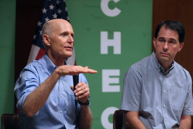 Florida U.S. Sen. Rick Scott, left, speaks at Heritage Action's Save Our Paycheck event with Scott Walker, former governor of Wisconsin, at Clifford's Supper Club in Hales Corners on Monday.