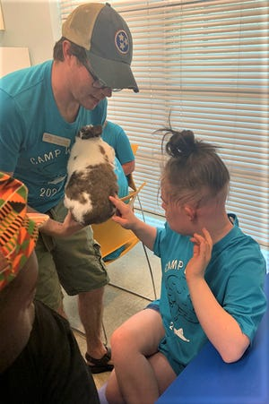Milana Goodpaster, right, pats a bunny during camp. She's one of 15 Rutherford County special education students who participated in a science camp with hands-on projects July 19-23 at Riverdale High and Discovery Center.
