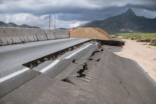 Road workers dump sand Monday, Aug. 16, 2021, on a blocked off piece of US 70 near mile marker 167 that collapsed after heavy rains overnight Friday.