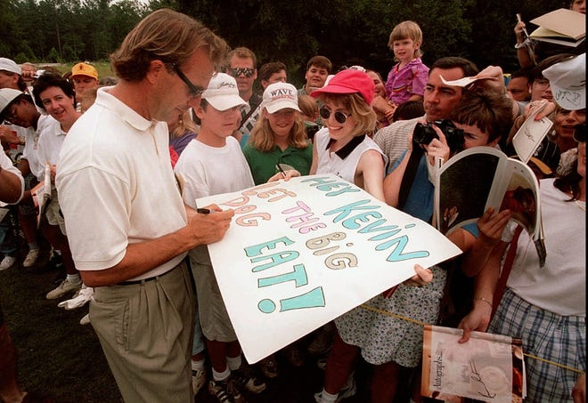 Kevin Costner signs an autograph on Kely Whitt's poster bearing a quote from Costner's new movie Tin Cup during play at the Jimmy V Celebrity Golf Classic in Cary, N.C.    The classic is held to raise funds for cancer research. (AP Photo/ Karl DeBlaker)