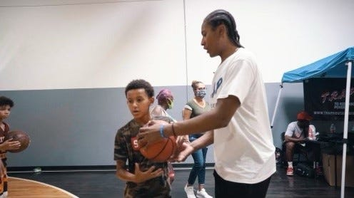 Aug. 14, 2021; TyTy Washington hands basketball to kid as his back-to-school charity event sponsored by T.R.A.P. House clothing at The Battleground basketball facility in Tempe, Ariz.