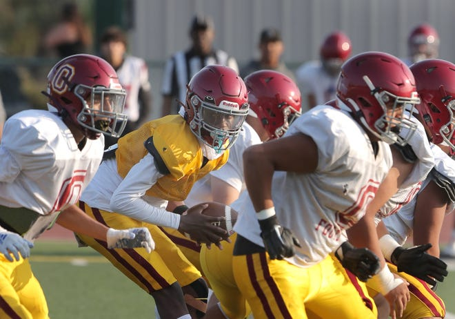 Surrounded by his offensive line, Oxnard High quarterback Devin Tate takes the snap during a scrimmage game against Ventura on Friday, Aug. 13, 2021.