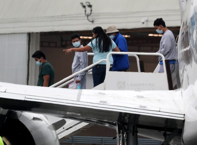 Young people board a bus after disembarking an airplane at Westchester County Airport Aug. 16, 2021. Westchester County Executive George Latimer said that the county airport is being used as part of a reunification effort between children crossing the U.S. and Mexico border and their parents.