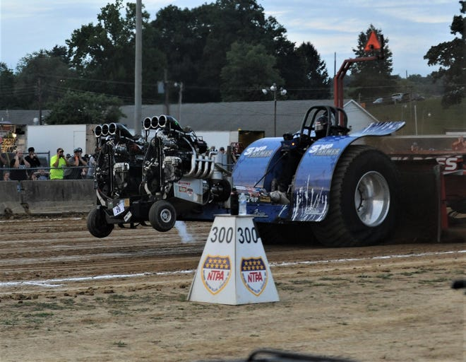 A modified tractor nears the end of its run during the NTPA Truck & Tractor Pull on Sunday night at the Muskingum County Fairgrounds. This was one of several grandstand events that will be held this week at the 175th Blue Ribbon Muskingum County Fair.