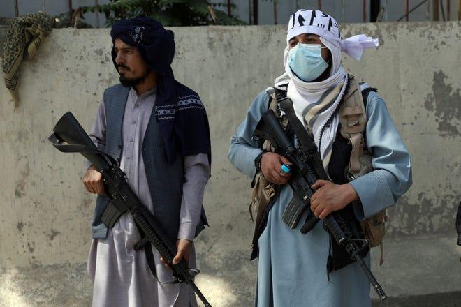 Combatientes talibanes montan guardia en la puerta principal que conduce al palacio presidencial afgano, en Kabul, Afganistán, el lunes 16 de agosto de 2021. El ejército estadounidense luchó para gestionar una evacuación caótica de Afganistán el lunes mientras los talibanes patrullaban la capital e intentaban patrullar .  Tranquilo después del derrocamiento del gobierno respaldado por Occidente.