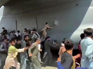 Hundreds of desperate Afghans run alongside a U.S. Air Force C-17 transport plane, some climbing on the plane, as it moves down a runway of the international airport in Kabul on Monday.