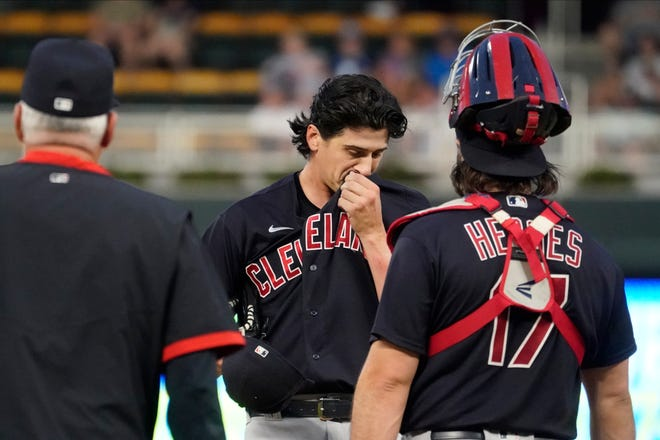 Cleveland pitcher Cal Quantrill, center, gets a mound visit in the third inning of a baseball game against the Minnesota Twins, Monday, Aug. 16, 2021, in Minneapolis. (AP Photo/Jim Mone)
