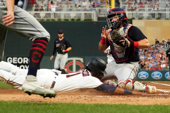 Minnesota Twins' Jorge Polanco beats the tag by Cleveland catcher Austin Hedges to score on a Josh Donaldson single in the third inning of a baseball game, Monday, Aug. 16, 2021, in Minneapolis. (AP Photo/Jim Mone)