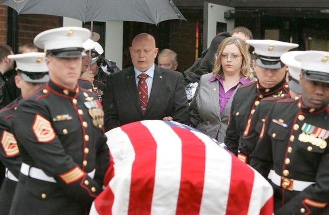 Robert Gilbert Sr., of Richfield, and his daughter, Ruth Ann Green, of Toledo, follow the casket of Marine Gunnery Sgt. Robert Gilbert II after a public funeral service March 28, 2010, at Revere High School in Richfield.