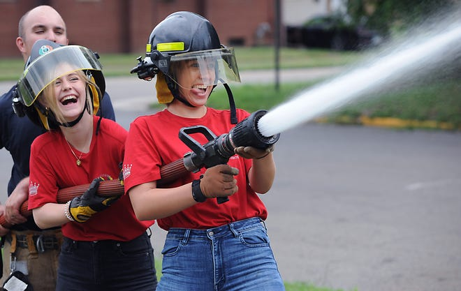 2021 Greater Alliance Carnation Festival Queen Torrie Forrest, left, and 1st Attendant Madeline Davis laugh as they work to control a fire hose Friday, Aug. 13, 2021, at the main fire station on Broadway Street.