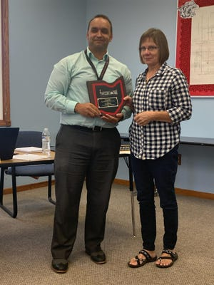 Superintendent Brad Romano presents Linda Landis with a plaque for her many years of service to the district.