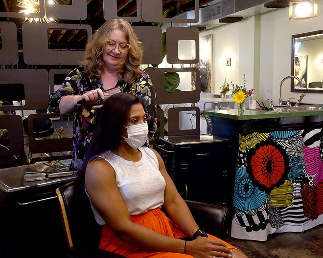 Elizabeth Jordheim, owner of Serendipity Salon and Gallery, styles Cortni Gonzales' hair Tuesday.