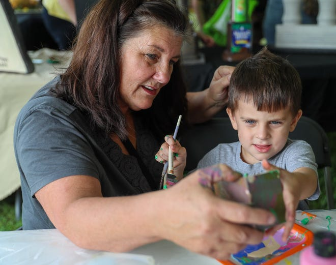 Charlie Sipes, 3 paints a birdhouse with help from his grandmother, Grove City resident Kim VanDerkar, at the Grove City Arts Council Pavilion at the Grove City EcoFest on Aug. 14. The annual event offered various activities that were related to environmental stewardship.